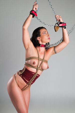Athletic nude brunette bound with ropes and chains Stock Photo - 13335478