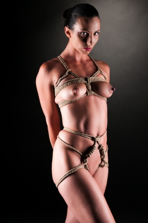 Athletic nude brunette bound with rope