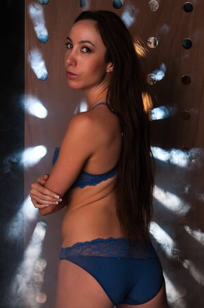 Beautiful young brunette in blue lingerie and smoke photo