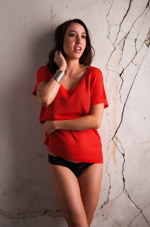 Beautiful young brunette against a cracked masonry wall Imagens