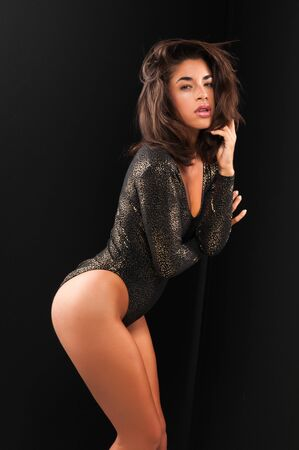 Beautiful young multiracial woman in black and gold photo