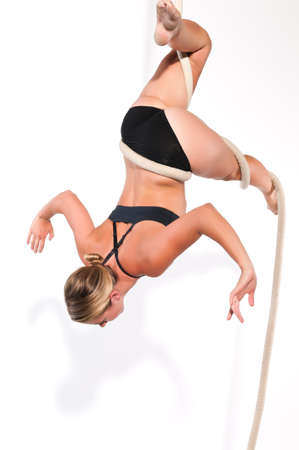 Athletic blonde aerialist suspended from a rope photo