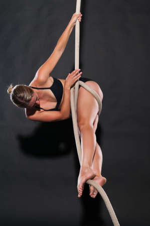 Athletic blonde aerialist suspended from a rope Stock Photo - 13805274