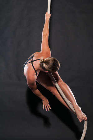 Athletic blonde aerialist suspended from a rope Stock Photo - 13805082