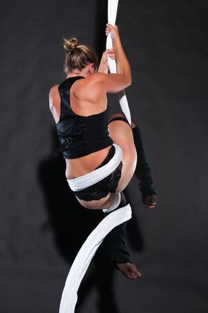 Athletic blonde aerialist suspended from white fabric