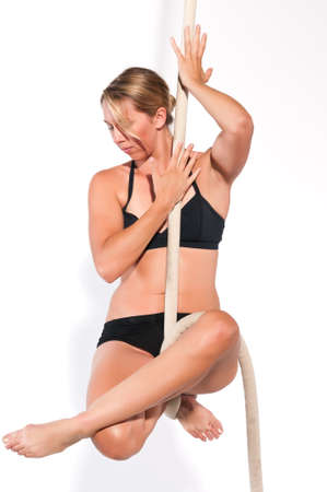 Athletic blonde aerialist suspended from a rope Stock Photo - 13830608