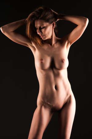 femme se deshabille: Belle grande brune nue dans l'ombre