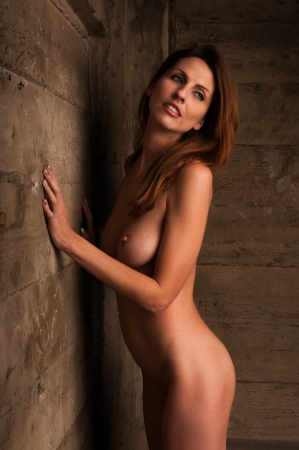 Sexy  woman naked: Beautiful tall nude brunette against an industrial wall Stock Photo