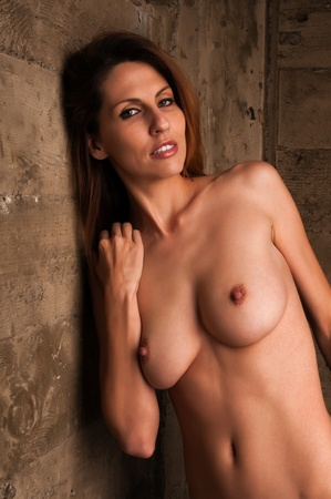 Beautiful tall nude brunette against an industrial wall Stock Photo