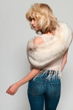 women in jeans: Pretty slim blonde in a fur stole and jeans