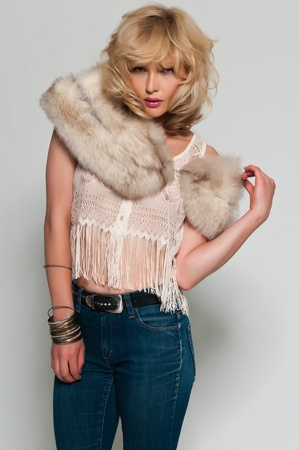 Pretty slim blonde in a fur stole and jeans photo