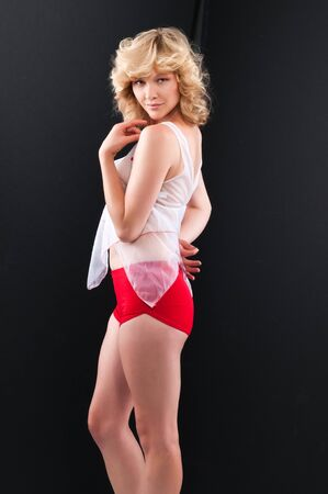 Pretty young blonde in a see through blouse and red shorts Imagens