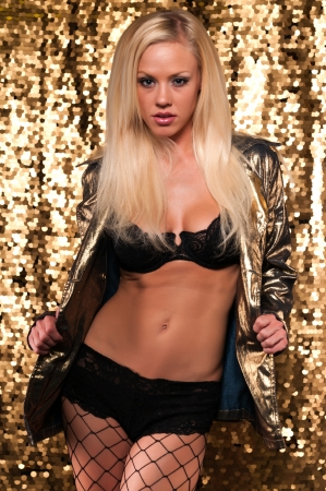fishnet stockings: Beautiful slender blonde in a gold jacket and black lingerie