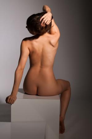 femme se deshabille: Petite brune assise nue sur un bloc blanc