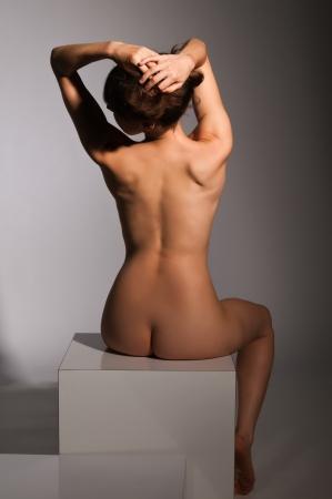 femme se deshabille: Petite brune nue assise sur un bloc blanc
