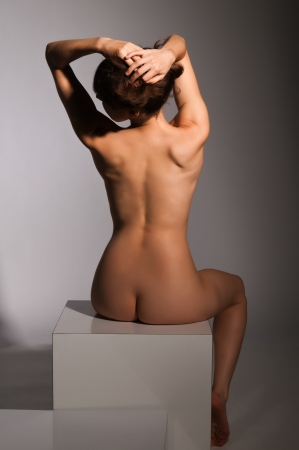undressed young: Petite nude brunette sitting on a white block