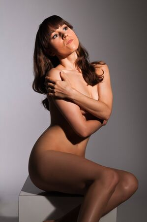 Petite nude brunette sitting on a white block Stock Photo - 14120431
