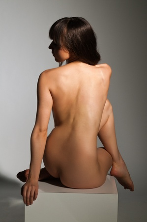 Petite nude brunette sitting on a white block Stock Photo - 14120436