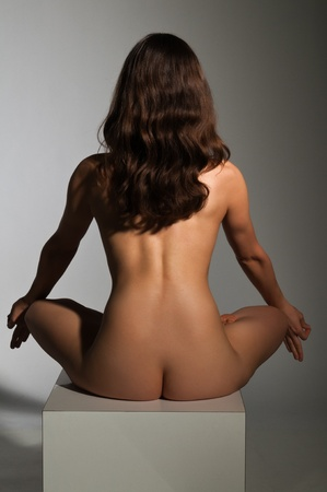 Petite nude brunette sitting on a white block Stock Photo - 14120433