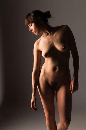 female nudity: Petite nude brunette standing in a narrow light