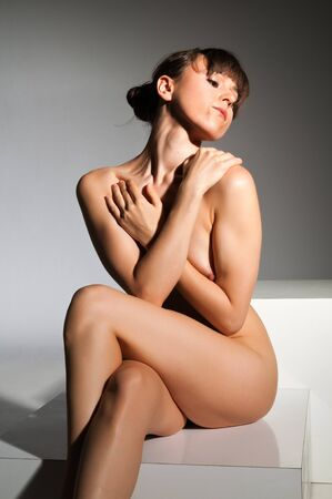 Petite nude brunette sitting on a white block Stock Photo - 14120463