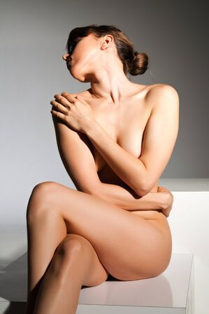 Petite nude brunette sitting on a white block Stock Photo - 14120461