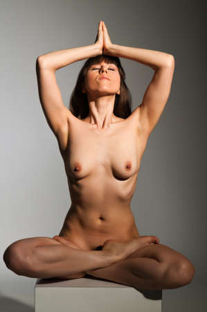 Petite nude brunette sitting on a white block Stock Photo - 14120464