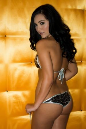 Beautiful petite brunette in a sequined bikini photo