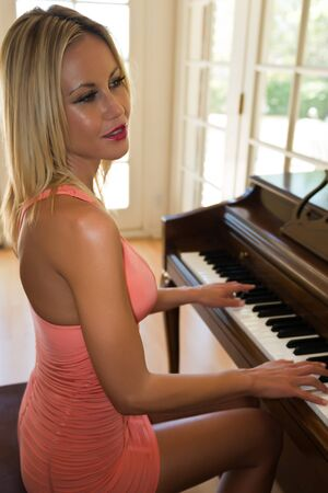 upright: Pretty slender blonde at an upright piano  Stock Photo