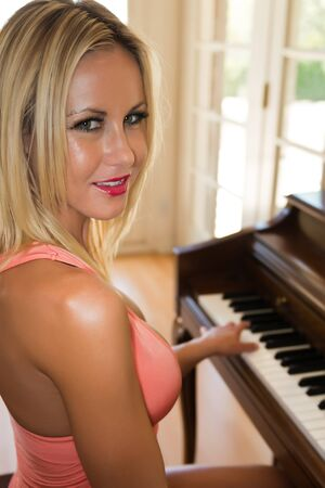 upright piano: Pretty slender blonde at an upright piano