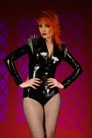 Beautiful pale redhead dressed in black latex photo