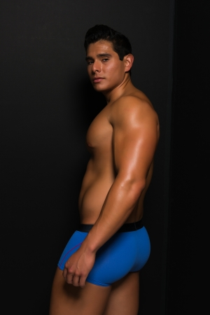 Athletic young man bare chested in blue briefs photo