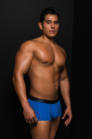 man in underwear: Athletic young man bare chested in blue briefs