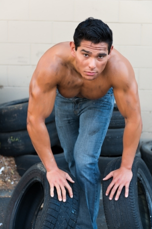 bare chest: Athletic young man with auto tires
