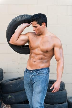 Athlétique jeune homme avec des pneus auto
