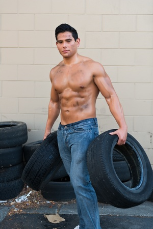 Athletic young man with auto tires photo