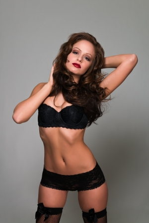 fishnets: Beautiful young brunette dressed in black lingerie Stock Photo