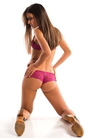 ひざまずく: ローズ色のランジェリーの美しい細長いルーマニア語ブルネット