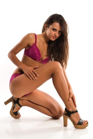 woman kneeling: Beautiful slender Romanian brunette in rose colored lingerie