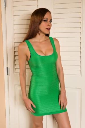 Pretty young redhead in a green sheath dress