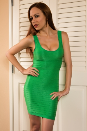 Pretty young redhead in a green sheath dress photo