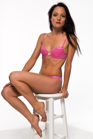 stool: Pretty slender brunette in pink and white lingerie Stock Photo
