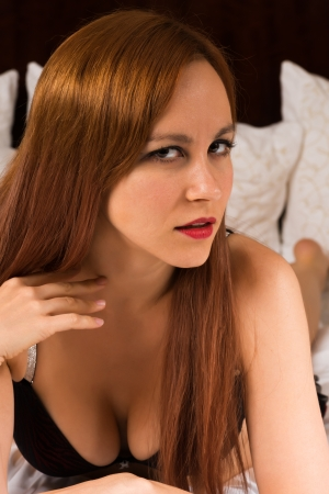 long shot: Pretty young redhead in red and black lingerie Stock Photo