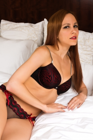 red panties: Pretty young redhead in red and black lingerie Stock Photo