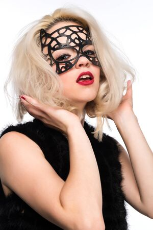 Pretty slender blonde in a black mask and fur vest photo