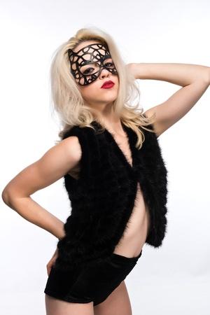 Pretty slender blonde in a black mask and fur vest