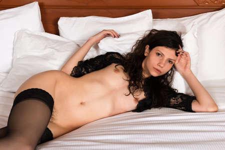 femme se deshabille: Svelte jeune femme brune dans une enveloppe noire