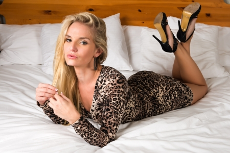sexy woman on bed: Pretty blonde woman in a leopard print dress