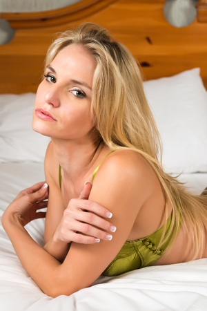undergarment: Pretty young blonde in metallic green lingerie Stock Photo