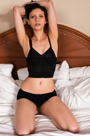 Slender young brunette dressed in black lingerie photo